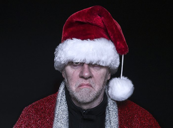 Bearded middle aged grumpy man in  Father Christmas fancy dress with Christmas hat and coat.